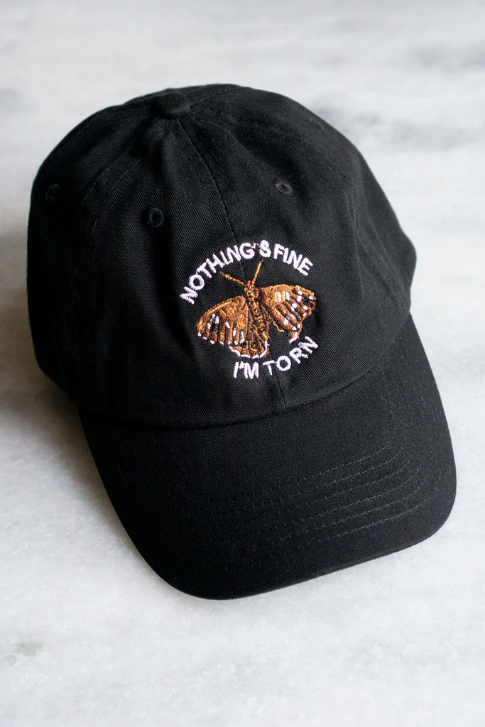 black baseball hat with white text reading nothing's fine I'm torn with brown moth in the middle with right wing torn at the bottom
