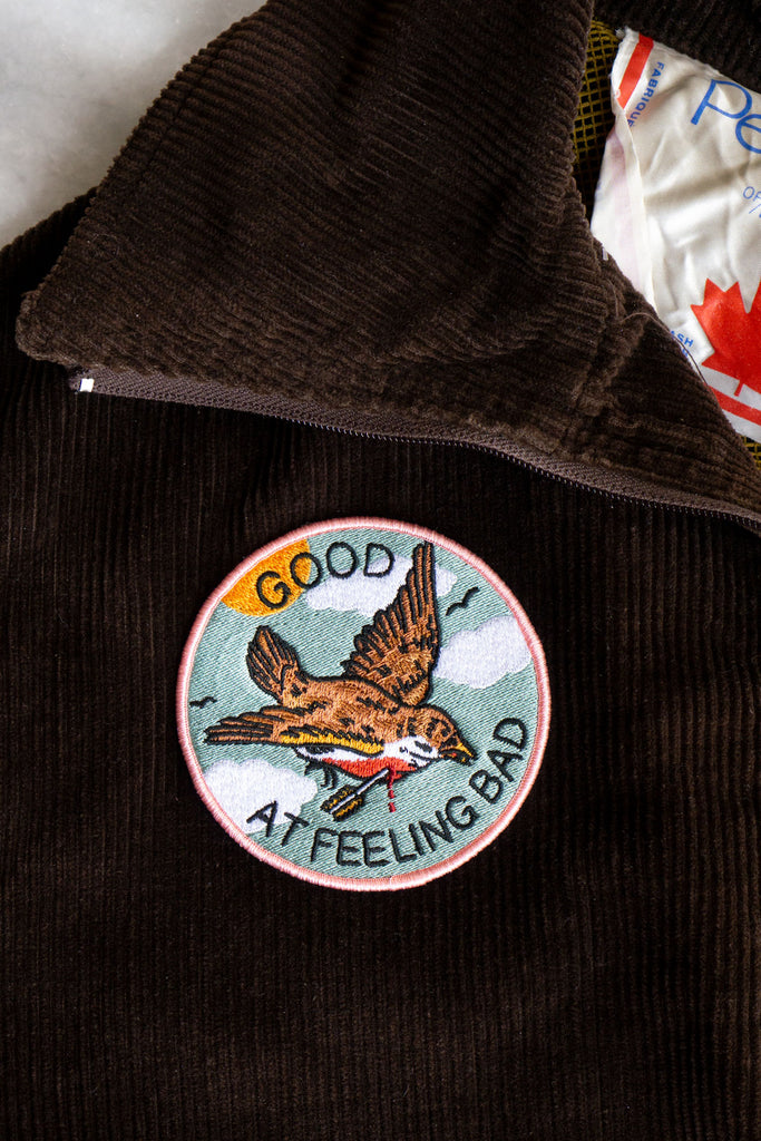 Brown corduroy jacket with a pale blue and pink patch with bird design on the chest