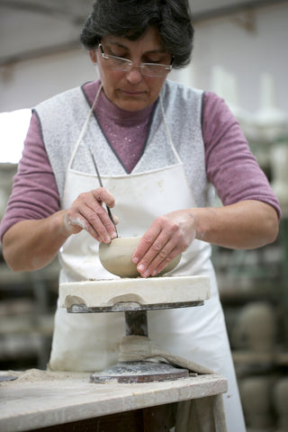The leftover material is being removed, and the bowl must dry before firing in the kiln.