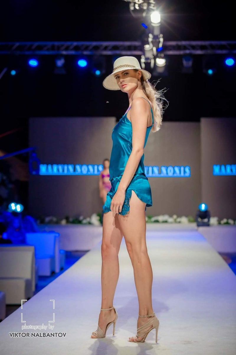 model in sky blue lingerie with light brown summer hat - side view