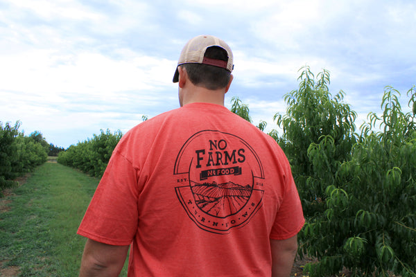 Mark Morgan, co-owner of Peach Pickin' Paradise, showing off Turnrows newest t-shirt, No Farms. No Food.