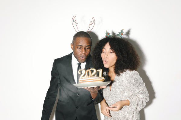 Young Black Couple blowing out 2021 candles on cake