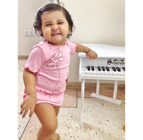 scohoenhut baby acoustic piano with a cute and laughing baby girl