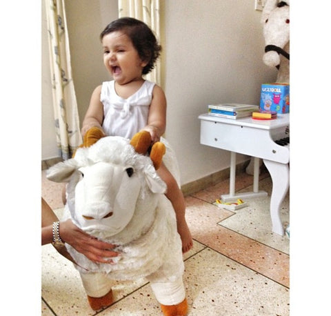 baby girl on a giant merino sheep