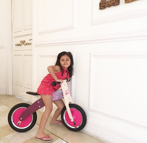 Toddler girl on a Janod wooden cycle. Sustainable toys