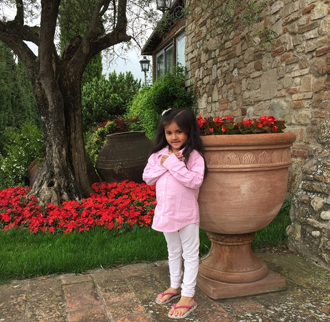 tuscan umbrian countryside with baby girl toddler in front of huge italian planter