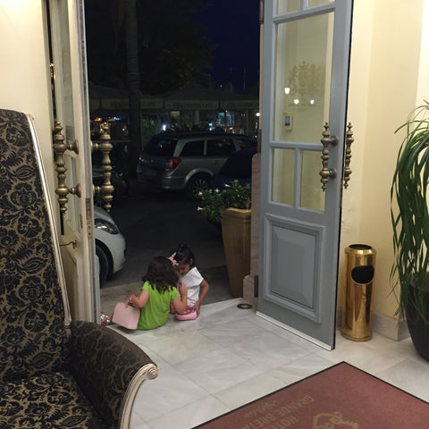 Two little girls saying good bye at Grande Bretagne Hotel, Nafplion greece. Jazz era town with little friendships, one world, vacation, travel, love.