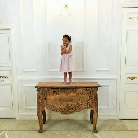 cute girl daughter standing french baroque rococo commode luxury furniture