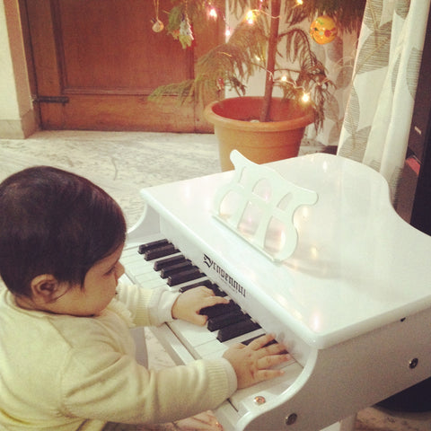 Little cute baby girl playing a white acoustic piano