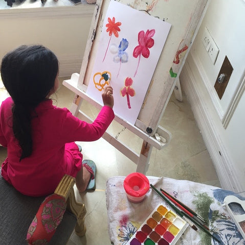 little girl painting with watercolors at home on an art easel.