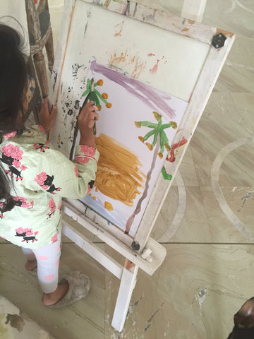 Baby painting art on an easel