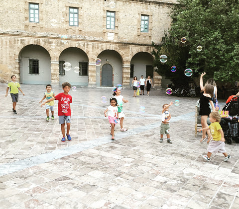 Children chasing bubbles at main square Nafplio, Greece. Travel, children, love, travel with children