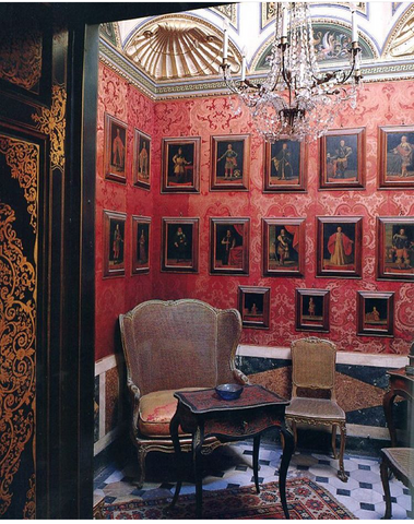small red wall papered reading room with frames and french louis xv chairs