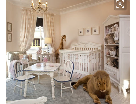 beautiful baby nursery with classic decor and oversized toys.
