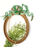 Frame in oval shape from The Unfurling with delicate ribbon