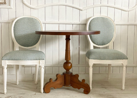 A set of two chairs with a petite table