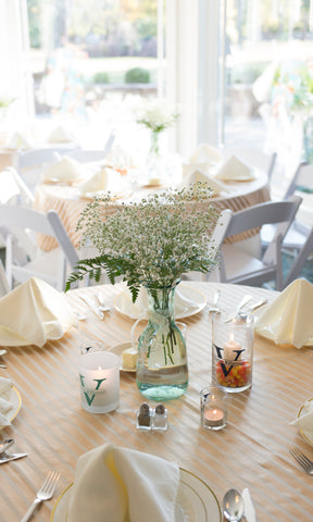 Wedding table centerpiece with floating candles and votive wedding favors