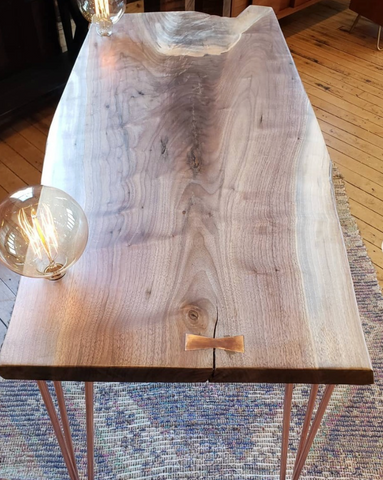 Walnut table with copper hairpins and Edison lights
