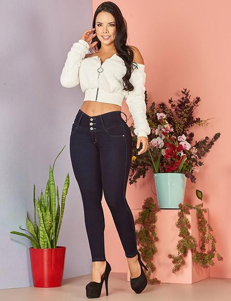 colombian woman with long hair wearing white zipper crop sweater and dark blue wash skinny jeans and black high heels