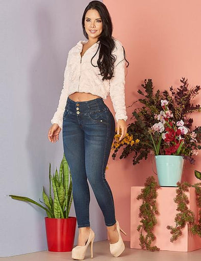 colombian woman with dark curly long hair with long sleeve white crop top and medium wash skinny blue jeans with nude high heels