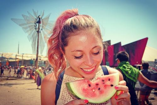Girl eating a watermelon at Lightning in a Bottle Festival