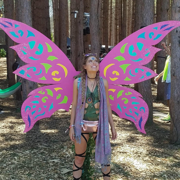 Girl wearing green top and black leg wraps in front of pink butterfly wings at Electric Forest