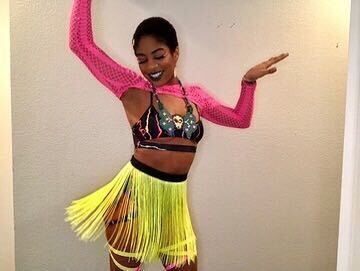 raver wearing a perler necklace, neon fringe skirt and pink mesh crop top