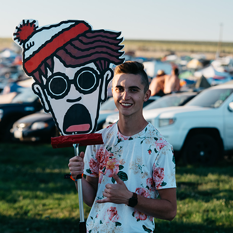 Raver wearing Men's all over print tee with floral pattern and holding a Where's Waldo Totem