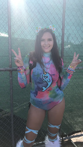 Rainbow Tie Dye bodysuit with white fluffies and narwhal perler at a Sunset Music Festival