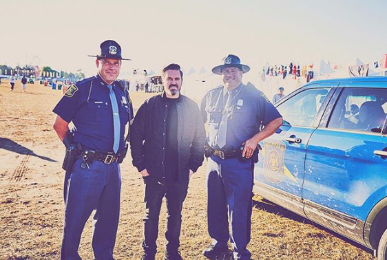 Pasquale Rotella posing with music festival security guards