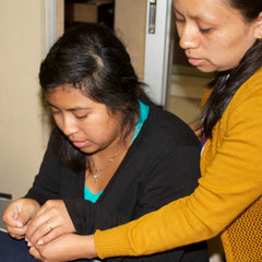 Lucia making a necklace with Chonita