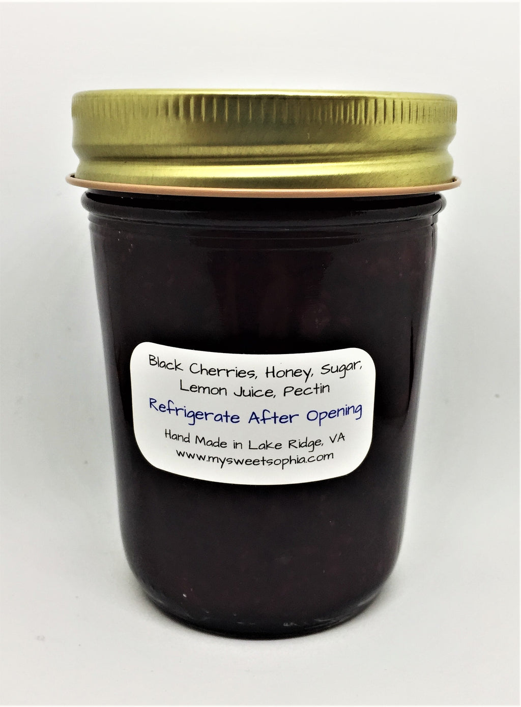 Glass jar with gold lid. Ingredients listed: Black Cherries, Honey, Sugar, Lemon Juice, Pectin.