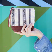 "Artisan made clutch purse featuring a unique boho Navajo design. The base of the wristlet purse is made out of hand-dyed 100% genuine leather, adding durability and style. The interior of the clutch is lined with 100% cotton. Wristlet strap is 100% leather.  6.5"" x 6.5"" White beige, black and maroon red interior lining. Will fit most phones and small wallets Brought to you by a collaboration with Los Angeles artist Bolt West"