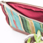 Hand-made clutch featuring a vibrant, southwestern pattern. Teal, Red, Yellow, Green and Purple.  The bottom of the clutch is made out of hand-dyed, 100% genuine cow hide, adding durability and style. The interior of the clutch is lined with 100% cotton.