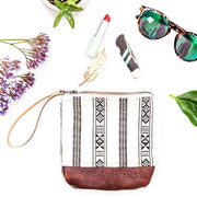 "Bolt West clutch purse featuring a unique boho Navajo design. The base of the wristlet purse is made out of hand-dyed 100% genuine leather, adding durability and style. The interior of the clutch is lined with 100% cotton. Wristlet strap is 100% leather.  6.5"" x 6.5"" White beige, black and maroon red interior lining. Will fit most phones and small wallets Brought to you by a collaboration with Los Angeles artist Bolt West"