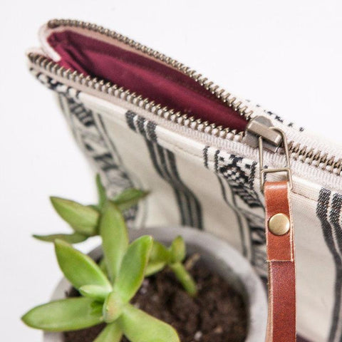 "Artisan made clutch featuring a boho Navajo design. The base of the clutch is made out of hand-dyed 100% genuine leather, adding durability and style. The interior of the clutch is lined with 100% cotton in maroon.  Wrist strap is 100% leather.  10.5"" x 6.5""  Genuine Hand Dyed Leather White/Beige background with black design Will fit most phones and wallets Brought to you by a collaboration with Los Angeles artist Bolt West."