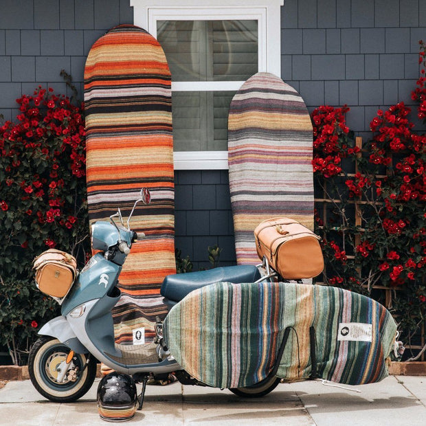 "Surfboards and Moped Vespa. Protect your surfboard while traveling to your favorite surf spot with this handwoven surfboard sock. Featuring a tight ribbed weave and a drawstring closure system, this surfboard bag is durable and enables you to quickly get your surfboard in or out.  Póvoa surfboard day bags are handmade in Póvoa, Portugal. The purchase of this surfboard bag supports small independent artisans.  Fits boards up to 22"" wide Fits longboards and shortboards (please choose exact size when ordering)"