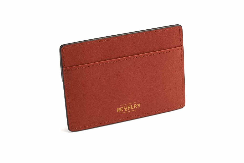 Image of a Emm coin and cash holder in Red Rust. This compact accessory has a dual sided function with a front buttoned compartment and cash and card slot on the backside. Crafted in smooth full grain cow leather, the Emm coin and cash holder in Red Rust is a fiery and intense hue, interesting on it's own but yet illustrates a sense of rich and robust sophistication to it. Each Emm coin and cash holder is internally lined with high quality woven gold fabric and is stitched together neatly in high quality to