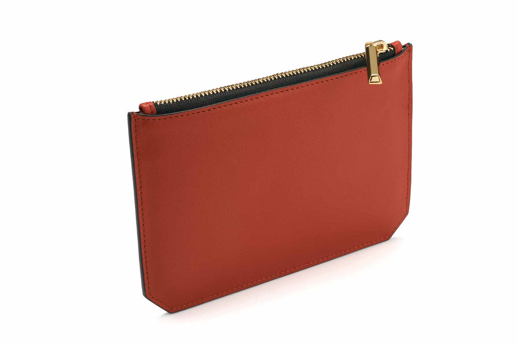 Image of luxury classic style pouch in Red Rust. Named as the Enn Pouch, this item is part of Revelry luxury small leather goods collection. The Enn Pouch is designed based on the prime handbag collection with geometrical cuts on the bottom edges of the pouch. Compact like a mini wallet, the Enn pouch design to replace most items stored in a regular-size wallet and is also useful for storing jewelry and makeup. The Enn Pouch is a complimentary accessory to use with any Revelry handbag. Useful during light t
