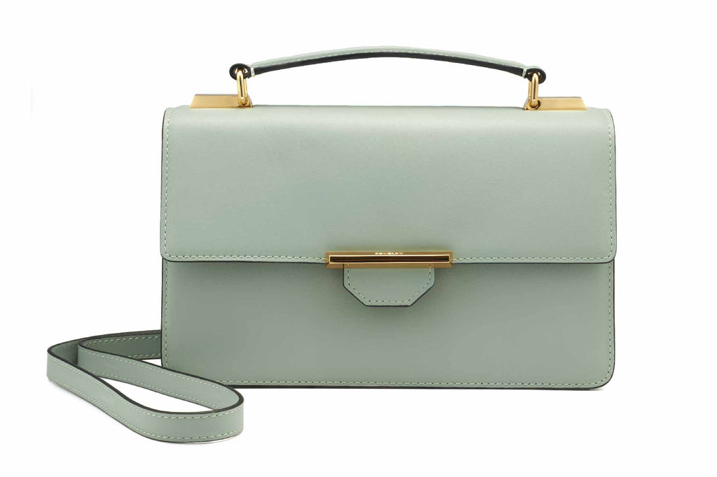 Image of a luxury classic clutch style crossbody shoulder handbag in Desert Sage. This luxury piece is call the Siren Crossbody and it's more than just a handbag to carry essentials. It is a fashion statement piece known for it's classy and casual style to transition into any occasions. Our Siren is Revelry's best selling item with just-the-perfect size and shape. The designs are classic and simple, favouring clean lines, a trending colour palette with a modern luxury finish. If you are a girl on the go who