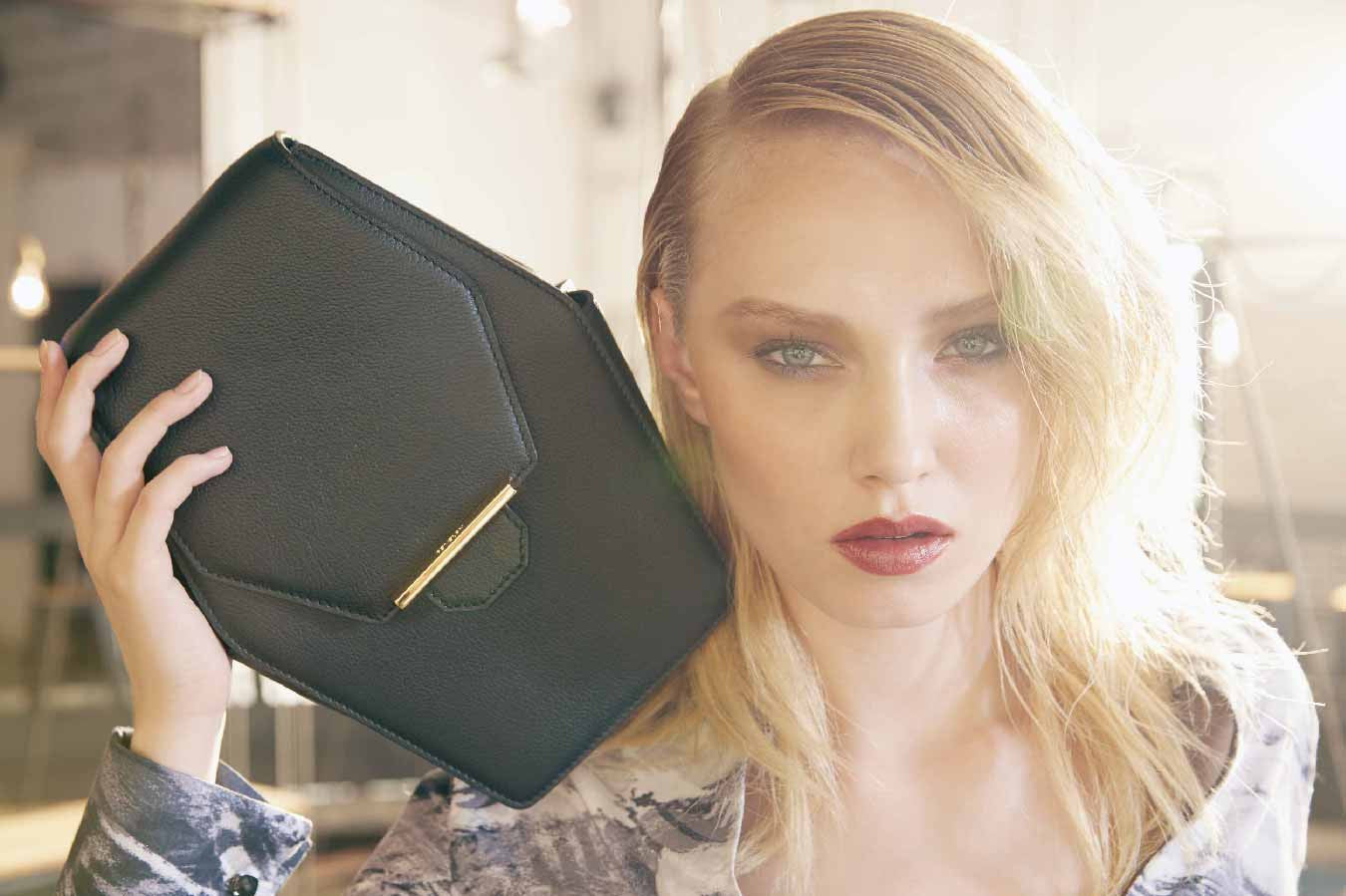 Close up image of a stunning model holding the luxury classic Rue Diamond shoulder handbag in Ebony (Black). Nothing speaks louder than the shape of this handbag; inspired by a diamond- beautiful and rare,  the Rue Diamond is Revelry's iconic style handbag. It is also the most unique piece in the range because of it's cut. Like an expensive diamond cut, the external front and back body of the Rue Diamond handbag is cut as one whole piece for a cleaner and luxury finish. The Rue Diamond has a distinctive style, edgily playful yet elegant. A sure wow factor for someone who is fashion conscious and daring to break any fashion boundaries. Can be teamed up with a casual daily look or bold and evening stylish look, the possibilities are limitless. Shaped like a diamond, the Rue is designed with a long front flap that wraps around from back to front. Both sides of the handbag features a small functional pocket that is enclosed with a small stud. The pocket is useful for keeping smaller items such as receipts, pen or cards.  The structure of the handbag is padded slightly for added comfort and is supported by a strong base to allow the handbag to stand on its own. With an adjustable shoulder strap, the Rue Diamond can be slung on the shoulder or across the shoulder. Alternatively, the shoulder strap can be removed for a clutch style look or double wrapped around the top flap for a top handle look. Whether it is worn casual or dressy, the Rue Diamond handbag makes any outfit distinctively striking. Designed in a textured full grain leather, the Rue Diamond comes in a deep black colour called Ebony; a mysterious and sophisticated color palette that evokes a sense of power and mighty. The choice of leather is captivated with a surrounding tonal oil edging and a mild supple sheen leather surface. This sleek handbag and distinctive silhouette has a combination of a firm front and back body and flexible sides for an elegant finish. The front features a top flap with an embellished 22 karat gold Revelry's exclusive gold bar hardware with subtle branding embossed at the top of the hardware. Custom mould in quality metal and plated in 22 karat gold, this Gold Bar hardware is a unique and innovative lock closure that serve as a design feature and secure lock function. The back features a stitching detailing that simulates the shape of the font flap to create an overall balance looking design. The interior of the Rue Diamond features a deep set compartment with ample spacing to fit most of your essentials, e.g. wallet, keys, mobile phone, notebook, lipsticks, pen and many more. The handbag comes with a widen sides to allow easy access into the narrow opening of the handbag. A back pocket is available to store and organise smaller items such as cards and receipts. Every piece is internally lined with high quality gold woven fabric at the internal compartment and back pocket while the rest of the interior body including top flap, facing and pocket binding is lined in textured full grain cow leather. An iconic Revelry logo is embossed in gold on the mid facing of the handbag for that designer luxury finish. Each handbag is crafted in meticulous detailing and luxury finish; with attention to detail on the stitching of the handbag. A luxury and unique masterpiece, the Rue Diamond shoulder handbag is a true gem on it's own and is available online at www.revelry-rvly.com
