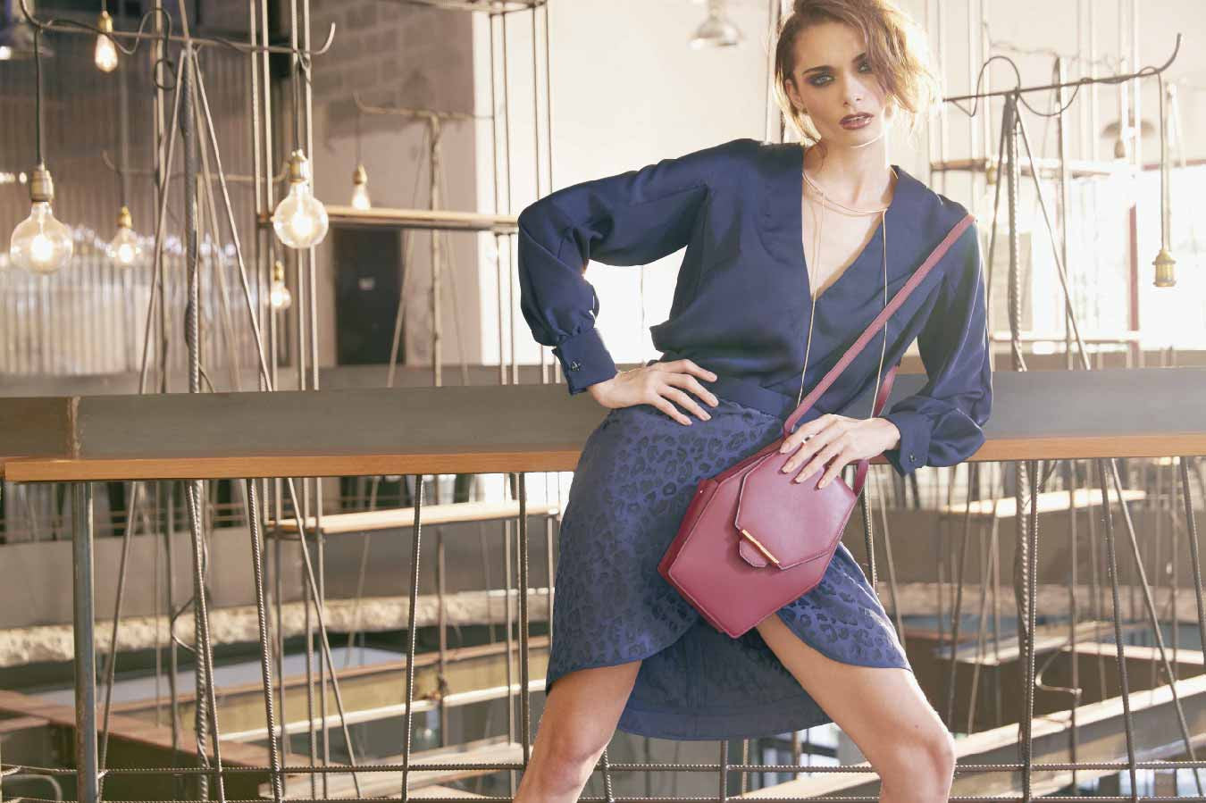 Image of a stunning model holding the luxury classic Rue Diamond shoulder handbag in Sangria (Plum). Nothing speaks louder than the shape of this handbag; inspired by a diamond- beautiful and rare,  the Rue Diamond is Revelry's iconic style handbag. It is also the most unique piece in the range because of it's cut. Like an expensive diamond cut, the external front and back body of the Rue Diamond handbag is cut as one whole piece for a cleaner and luxury finish. The Rue Diamond has a distinctive style, edgily playful yet elegant. A sure wow factor for someone who is fashion conscious and daring to break any fashion boundaries. Can be teamed up with a casual daily look or bold and evening stylish look, the possibilities are limitless. Shaped like a diamond, the Rue is designed with a long front flap that wraps around from back to front. Both sides of the handbag features a small functional pocket that is enclosed with a small stud. The pocket is useful for keeping smaller items such as receipts, pen or cards.  The structure of the handbag is padded slightly for added comfort and is supported by a strong base to allow the handbag to stand on its own. With an adjustable shoulder strap, the Rue Diamond can be slung on the shoulder or across the shoulder. Alternatively, the shoulder strap can be removed for a clutch style look or double wrapped around the top flap for a top handle look. Whether it is worn casual or dressy, the Rue Diamond handbag makes any outfit distinctively striking. Designed in a smooth full grain cow leather, the Rue Diamond comes in a rich plum colour called Sangria; an exotic red that evokes a sense of rich adventure and majestic luxury. The choice of leather is captivated with a surrounding tonal oil edging and a mild supple sheen leather surface. This sleek handbag and distinctive silhouette has a combination of a firm front and back body and flexible sides for an elegant finish. The front features a top flap with an embellished 22 karat gold Revelry's exclusive gold bar hardware with subtle branding embossed at the top of the hardware. Custom mould in quality metal and plated in 22 karat gold, this Gold Bar hardware is a unique and innovative lock closure that serve as a design feature and secure lock function. The back features a stitching detailing that simulates the shape of the font flap to create an overall balance looking design. The interior of the Rue Diamond features a deep set compartment with ample spacing to fit most of your essentials, e.g. wallet, keys, mobile phone, notebook, lipsticks, pen and many more. The handbag comes with a widen sides to allow easy access into the narrow opening of the handbag. A back pocket is available to store and organise smaller items such as cards and receipts. Every piece is internally lined with high quality gold woven fabric at the internal compartment and back pocket while the rest of the interior body including top flap, facing and pocket binding is lined in smooth full grain cow leather. An iconic Revelry logo is embossed in gold on the mid facing of the handbag for that designer luxury finish. Each handbag is crafted in meticulous detailing and luxury finish; with attention to detail on the stitching of the handbag. A luxury and unique masterpiece, the Rue Diamond shoulder handbag is a true gem on it's own and is available online at www.revelry-rvly.com