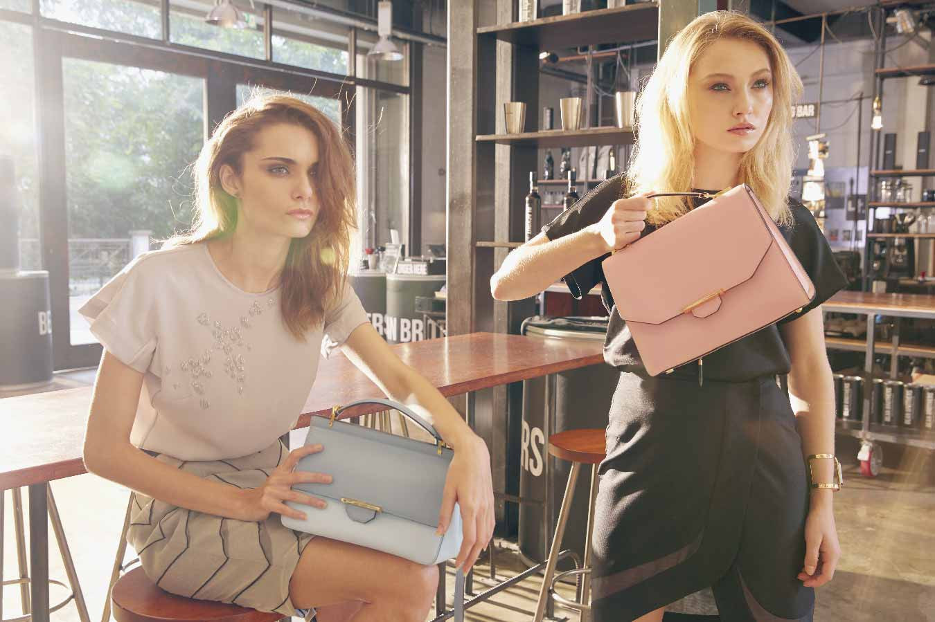Image of stunning models carrying a luxury Divine two tone leather shoulder handbag in Dusty Blues and  classic style Vix Trapeze leather shoulder handbag in Dusty Pink. The Divine Two Tone is a breathtaking handbag with many features including a luxury collection of 22 karat gold plated hardware and beautiful line of custom made leather with a luscious feel to it. The handbag is designed with an A-framed with soft folds on both sides of the leather. This gives the handbag a softer and feminine appearance to the wearer. The Divine two tone can be tote with a slim top handle or sling around the shoulder for a more casual look, making it the perfect handbag to complete any look from day to evening. Crafted with a two tone custom dyed smooth full grain cow leather, the lighter blue leather is featured on the lower front and back of the handbag while the darker blue leather is featured on the top flap, top back facing, top handle and long shoulder strap. This cool and calming color combination creates a fresh and feminine styling to any outfit. It also evokes a sense of lightness and freedom to allow one to feel more confident in their choice of outfit. Each handbag is embellished with the iconic Revelry gold bar lock closure hardware for the added secure and functionality. It also features a unique dual function hardware with an added triangle shaped ring holder. Attached to the ring is a long strap with a detachable snap hook designed in a unique shape to clipped in with the ring. The top spine of the handbag is crafted with a solid foundation to withhold and strengthen the placement of the top handle hardware. Every piece of hardware is embossed with the iconic Revelry logo for a luxury finish.The feature on the interior part of the handbag includes the internal flap and facing of the handbag lined with a contrasting custom dyed light blue in smooth full grain cow leather. An iconic Revelry logo is embossed on the internal facing part of the handbag in luxury gold. Each handbag has a spacious compartment to store all your necessities and is lined in a luxury woven gold fabric. The inside compartment also features an internal back pocket to store smaller items and is lined with a luxury woven gold fabric and contrasting custom dyed light blue leather trimming. All handbags are displayed with a clean and neat stitching detailing finish. The Vix Trapeze is one of Revelry's luxury handbag that is an evergreen and versatile style to carry all year round, and transition form a day to night look. The handbag design is kept simple, clean and elegant with a luxury finish. This stunning handbag is meticulously crafted with high quality leather and delicately stitched together with high quality threading. All stitching details are finished clean and neat for a luxury high end look. Crafted in a beautiful Dusty Pink smooth full grain cow leather, this stunning leather type and color are carefully selected to achieve a classic and luxury finish. It has a mild sheen and soft finish with contrasting dark oil edging used throughout the handbag to allow the Dusty Pink to stand out. Known to be a popular trending color, it carries a gentle, compassionate, composed, reflective and lighthearted trait. Each handbag features a slim top handle and a detachable long strap that can be adjusted to a suited length. Whether you prefer to tote it or wear it across your shoulder, both looks are versatile for any occasion. The iconic Revelry gold bar hardware is embellished at the front flap of the handbag and is designed with an innovative lock closure for secured functionality. A smaller Revelry gold bar ring is also attached on both sides of the top handle with the Revelry's logo embossed on the inside of the bar. The bottom base of the handbag has a wide panel that supports the overall structure of the handbag with five rivets attached to the base to protect the bottom leather from dirt or scuff marks. Each individual rivet is embossed in the iconic Revelry logo around it. Every piece of hardware used on the Vix Trapeze are plated in 22 karat gold. The interior body of the Vix Trapeze features a spacious and versatile compartment area to carry a heap of necessities, e.g. wallet, mobile phone, iPad, makeup bag, pen, notebook and many more. It also comes with a wide back pocket to store smaller items such as card or receipts. The Internal flap, facing and pocket trimming of the handbag are all lined in smooth full grain cow leather while the rest of the internal compartment area are lined in high quality woven gold fabric. To purchase one of Australian luxury leather accessories, shop for Revelry online at www.revelry-rvly.com.