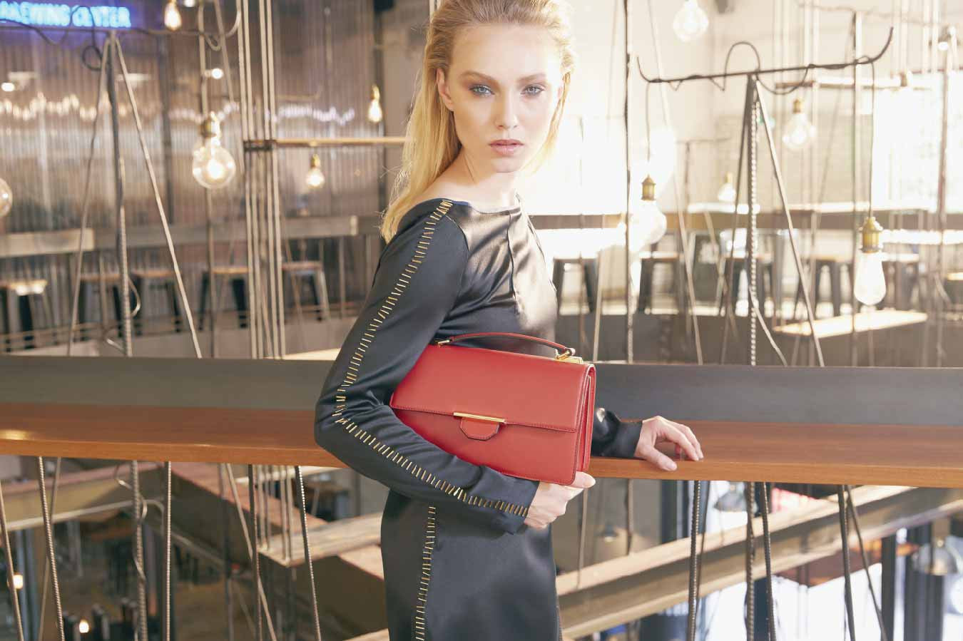 "Image of a stunning model with a luxury classic style Siren Crossbody leather shoulder handbag in Red Rust. This luxury piece is more than just a handbag to carry essentials, it is a fashion statement piece known for it's classy and casual style to transition into any occasions. Our Siren is Revelry's best selling item with just-the-perfect size and shape. The designs are classic and simple, favouring clean lines, a trending colour palette with a modern luxury finish. If you are a girl on the go who needs something small that will fit a wallet and a few essentials, this handbag is a definite go for you. There is something so fresh and chic about red accessories to add colour into your world. Designed in a small rectangular size with a front flap, this structure holds more than enough essentials for a comfortable hands-free wear. The long strap is not only detachable but adjustable to suit any length to the wearer. Sling it on or across the shoulder, it's weekend to weekday possibilities. A top handle is also available if you prefer a modern hand held clutch style to polish your everyday look. The Siren Crossbody handbag comes in a stunning supple leather and sleek design that captures a downtown cool and sophistication, but also completely approachable. Covered in high quality smooth grain cow leather, the spicy flavour earth hue is a stylish tone that emanate luxury and sophistication. Hence the name ""Red Rust"", dramatic and rich. With a mild sheen, the leather is also enhanced with dark oil edging finishing around the handbag. The structure of the handbag is padded subtly to add a soft luscious feel to the already-smooth supple leather. A Revelry handbag is incomplete without it's signature iconic Gold Bar inspired hardware. Each Gold Bar is plated in 22 karat gold and has the Revelry logo embossed at the top. This piece of hardware highlights the simplicity and minimalism of the design of the handbag. It functions both as a design feature and secure lock closure. Like it's signature iconic front Gold Bar inspired hardware, the top handle lands its design from it. The top handle hardware is a smaller Gold Bar with a square ring attached to it. Comes in a pair, the top handle is attached to both ends of the square rings. All hardwares are plated in 22 karat gold and subtle branding is embossed on the inner corner of the Gold Bar for that luxury designer finish. The internal of the handbag features 2 equal seperate compartment areas for storing and organising the necessary essentials, e.g. wallet, mobile phone, keys, lipstick, pen, tissues or anything that is compact and practical. A wide pocket is also available at the back to store smaller items such as business cards or receipts. This stunning handbag is stitched together with quality tonal threading and every piece is finished with clean and neat attention to detail. The internal body is covered in a combination of smooth full grain cow leather and high quality woven gold fabric. The top flap, facing and pocket trimming are leather lined while the remaining internal part of the body is lined in gold fabric. An iconic Revelry logo is embossed on the lower mid area of the flap for that luxury designer finish. A best selling style, the Siren Crossbody handbag is available online at www.reverly-rvly.com."