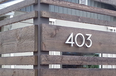 modern house numbers on wood fence 403