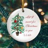 "A personalised circular ceramic Christmas decoration with an illustration of a Christmas tree and the words ""All I want for Christmas is you Liam"" in red script text printed onto it."