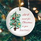 "A personalised circular ceramic Christmas decoration with an illustration of a Christmas tree and the words ""All I want for Christmas is you Rachel"" in red script text printed onto it."