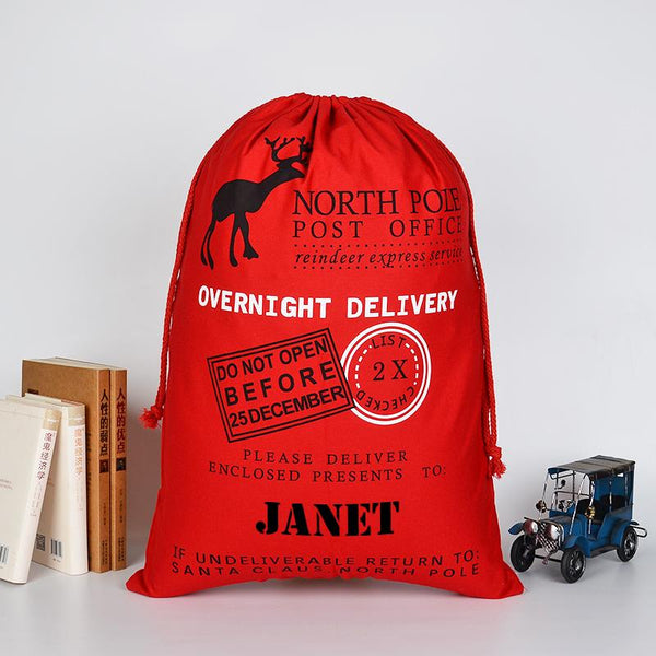 A personalised red Christmas sack with a vintage style postage design and a child's name printed at the bottom.