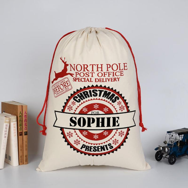 A personalised Christmas postage themed cotton sack with a child's name added to the design.