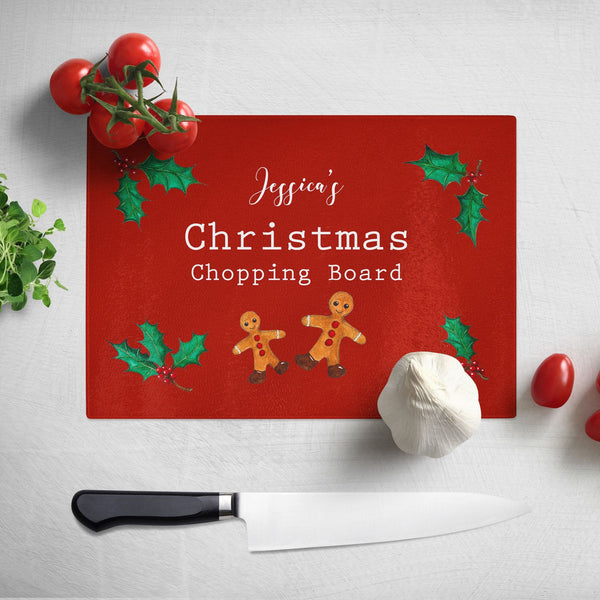 "A personalised Christmas chopping board. The chopping board has a red background and a pattern of gingerbread men and holly leaves. The design includes white text which reads ""Jessica's Christmas chopping board"""
